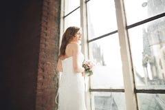 Элегантная красивая невеста свадьбы представляя около большого свода окна Стоковая Фотография RF