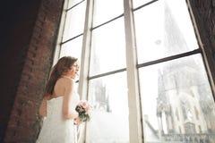 Элегантная красивая невеста свадьбы представляя около большого свода окна Стоковое Фото