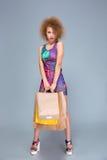Элегантная курчавая молодая женщина с много хозяйственных сумок Стоковое Изображение