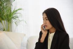 Элегантная молодая бизнес-леди говоря на мобильном телефоне сидя на белой софе с серьезным выражением стоковые изображения rf