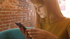 Элегантная молодая женщина беседуя на сенсорной панели пока сидящ в удобной кофейне акции видеоматериалы