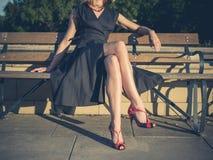 Элегантная молодая женщина сидя на скамейке в парке Стоковые Изображения