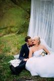 Элегантная молодая счастливая пара свадьбы сидит на зеленой траве дальше Стоковая Фотография RF