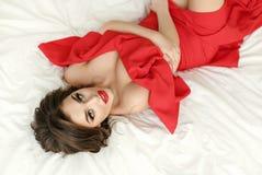 Элегантная сексуальная девушка брюнет в красном платье лежит на кровати стоковое фото