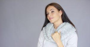Элегантная середина постарела женщина представляя с шерстяным теплым шарфом