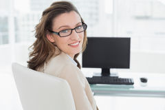Элегантная усмехаясь коммерсантка на столе офиса Стоковое Изображение RF