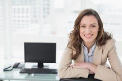 Элегантная усмехаясь коммерсантка сидя на столе офиса Стоковые Изображения RF