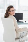 Элегантная усмехаясь коммерсантка сидя на столе офиса Стоковое Изображение