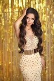Элегантное брюнет в золотом платье вечера Стиль очарования моды Стоковые Фотографии RF