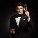 Элегантное holdinh человека вверх по стеклу шампанского Стоковая Фотография RF