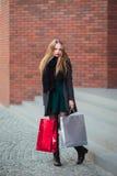 Элегантные молодые красивые женщины держа хозяйственные сумки, идя далеко от магазина Продажа, защита интересов потребителя и кон Стоковые Изображения RF