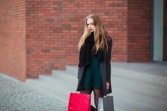 Элегантные молодые красивые женщины держа хозяйственные сумки, стоя на лестницах магазина Продажа, защита интересов потребителя и Стоковые Изображения