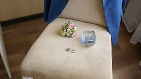 Элегантные люди вспомогательные для wedding, вода туалета с петлицей лежат на стуле, его смертной казни через повешение куртки на видеоматериал