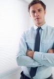 Элегантный бизнесмен при оружия пересеченные в офис Стоковая Фотография