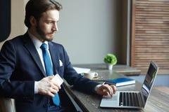 Элегантный бизнесмен работая с компьтер-книжкой в кафе Стоковое Фото