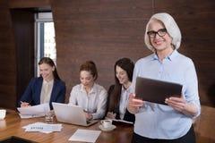 Элегантный босс представляя с ее коллегами Стоковое Изображение RF