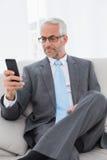 Элегантный зрелый обмен текстовыми сообщениями бизнесмена на софе Стоковые Изображения RF