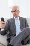 Элегантный зрелый обмен текстовыми сообщениями бизнесмена дома Стоковые Фотографии RF