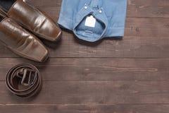 Элегантный комплект: коричневые ботинки ` s людей, коричневый кожаный пояс, голубая рубашка, Стоковая Фотография RF