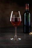 Элегантный красный бокал и бутылка вина Стоковое Фото