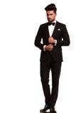 Элегантный молодой человек моды регулируя его смокинг стоковая фотография rf