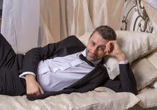Элегантный плейбой возлежа на кровати стоковые изображения