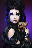 Элегантный темный ферзь с маленькой собакой над темной предпосылкой Стоковое Фото