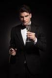 Элегантный человек держа бутылку и стекло шампанского Стоковое Фото