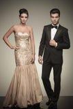 Элегантный человек и женщина представляя на серой предпосылке студии стоковая фотография rf