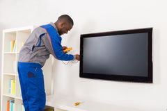 Электрик проверяя телевидение с вольтамперомметром стоковые фотографии rf