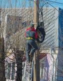 Электрик работника работая с проводами в улице стоя на лестницах на коле Стоковое Изображение RF