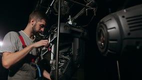 Электрик ремонтирует оборудование освещения на этапе видеоматериал