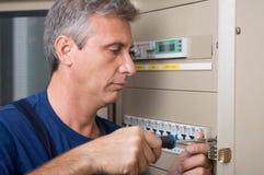 Электрик ремонтируя автомат защити цепи стоковые изображения rf