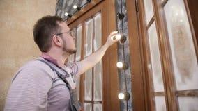 Электрик устанавливает шарик в осветительную установку на декоративную стену видеоматериал