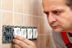 Электрик устанавливая электрическое compone приспособления или штепсельной вилки стены Стоковая Фотография RF
