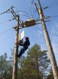 Электрик для того чтобы обслуживать управление reclosers на поляках напряжения тока стоковое фото
