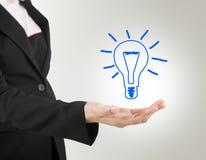 Электрическая лампочка в бизнес-леди руки. стоковые изображения rf