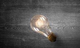 Электрическая лампочка на деревянной поверхности Мультимедиа Стоковое Фото
