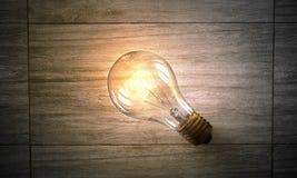 Электрическая лампочка на деревянной поверхности Мультимедиа Стоковые Изображения RF