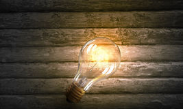 Электрическая лампочка на деревянной поверхности Мультимедиа Стоковые Фото