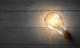 Электрическая лампочка на деревянной поверхности Мультимедиа Стоковое Изображение RF
