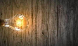 Электрическая лампочка на деревянной поверхности Мультимедиа Стоковая Фотография RF