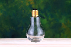 Электрическая лампочка на деревянной поверхности с зелеными предпосылками Стоковые Фотографии RF