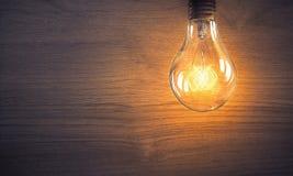Электрическая лампочка на деревянной поверхности Стоковые Изображения RF