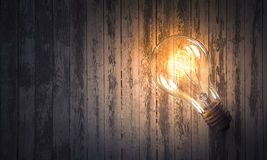 Электрическая лампочка на деревянной поверхности Стоковые Фотографии RF
