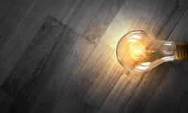 Электрическая лампочка на деревянной поверхности Стоковое Изображение RF