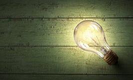 Электрическая лампочка на деревянной поверхности Стоковые Фото
