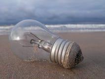 Электрическая лампочка на песке в пляже Стоковое Изображение RF