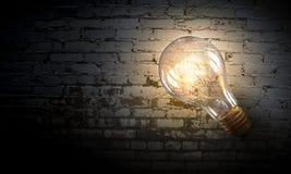 Электрическая лампочка на поверхности кирпича Мультимедиа Стоковые Изображения