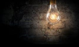 Электрическая лампочка на поверхности кирпича Мультимедиа Стоковое фото RF